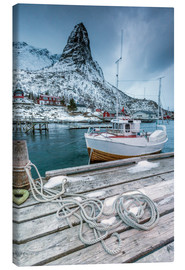 Lienzo  A boat moored in the cold sea in the background the snowy peaks. Reine. Lofoten Islands Northern Nor - Roberto Moiola